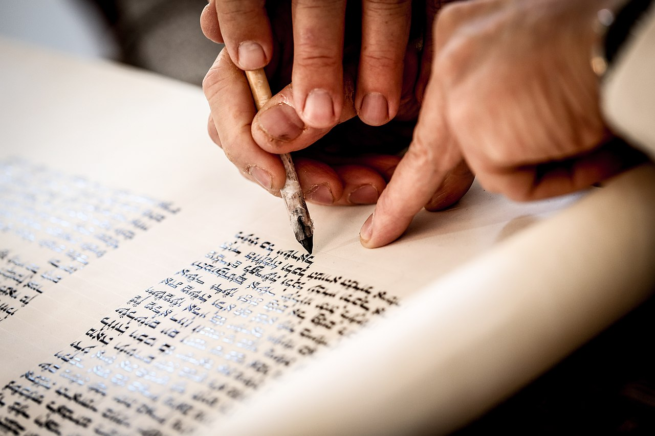 Hands of a scribe holding a quill and touching it to.a Torah scroll.