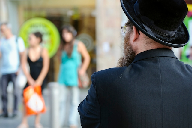 Jerusalem, Israel - October 6, 2010: At a crosswalk on King George Street, an Orthodox Jew waits to cross. On the other side of the street are secular Israelis waiting to cross.