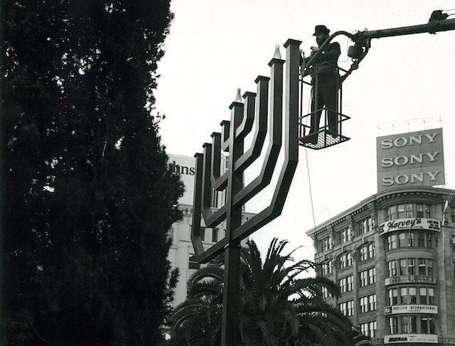 Chabad-Lubavitch Rabbi Chaim Drizin, kindles the Hanukkah menorah at a public menorah lighting ceremony in Union Square in San Francisco in 1975. (Courtesy Chabad.org)