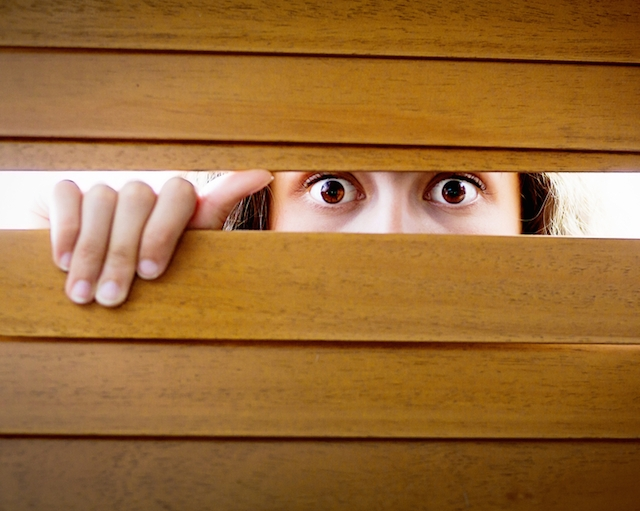 Startled and worried girl looks through wooden blinds, wide eyed