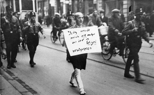 "Jewish lawyer Michael Siegel is forced to march barefoot with a placard reading, ""I will never again complain to the police,"" March 1933 in Munich. (Heinrich Sanden/German Federal Archives)"