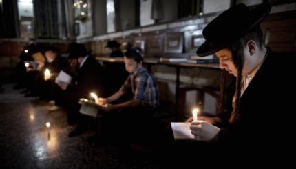 Ultra-Orthodox Jewish men use a candle l