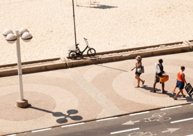 Tel-Aviv, Israel - August 18th, 2012: High angle view of three people walking on the boardwalk by the beach in Tel-Aviv on a hot summer day.