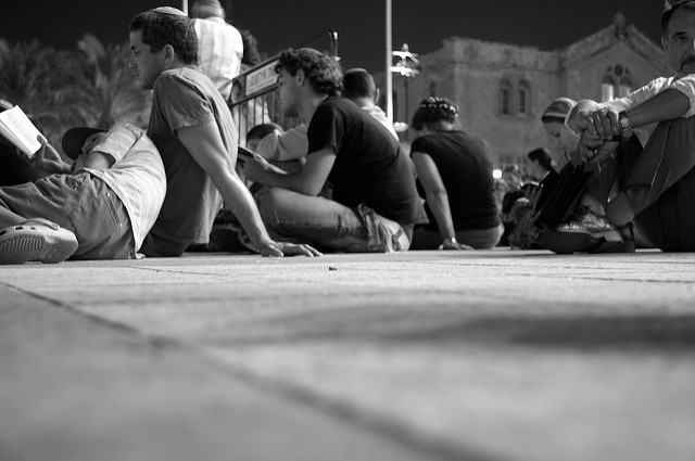 Israelis listen to the Lamentations while sitting on the ground, a sign of mourning, at a square in Jerusalem. (Yosef Silver/Flickr)