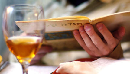 Man reads in the Haggadah book during Passover Seder dinner.