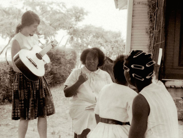 Heather Booth playing guitar for Fannie Lou Hamer during the Freedom Summer Project in Mississippi, 1964. (Wallace Roberts via Flickr)