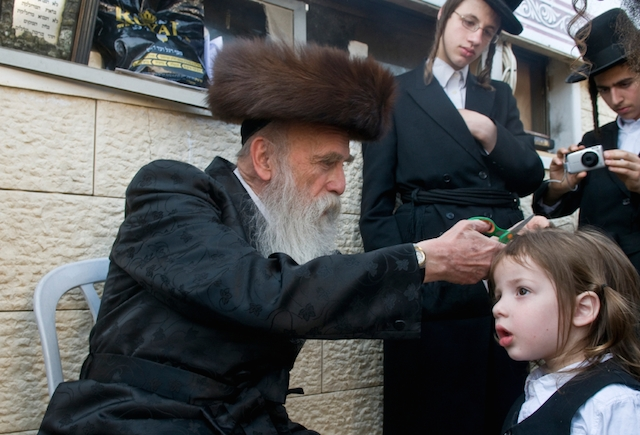 Rabbi cuts child's hair in a Lag Ba'Omer ceremony in Bar Yochai tomb in Meron , Israel on May 10 2012 . (iStock)