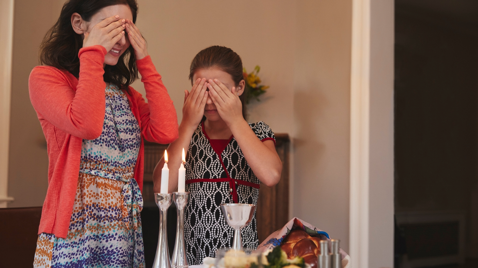 Jewish girl and mother cover eyes to recite Shabbat blessing