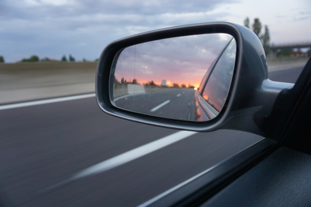 Beautiful sunset in a car side mirror on highway