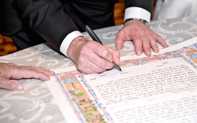 Bride and groom signing a katuba in front of a Rabbi during their wedding ceremony