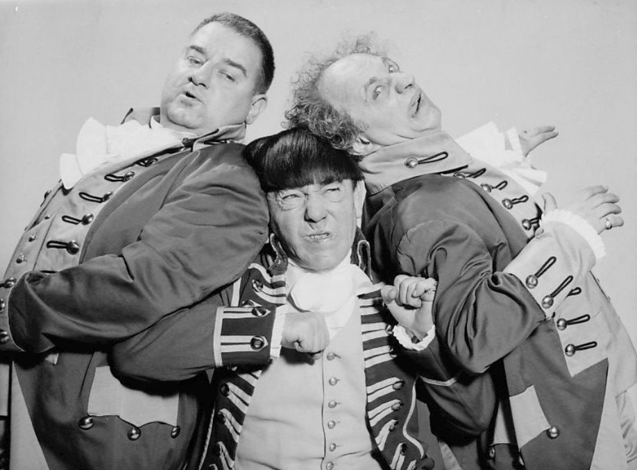 Three men in costume leaning on one another a grimacing.