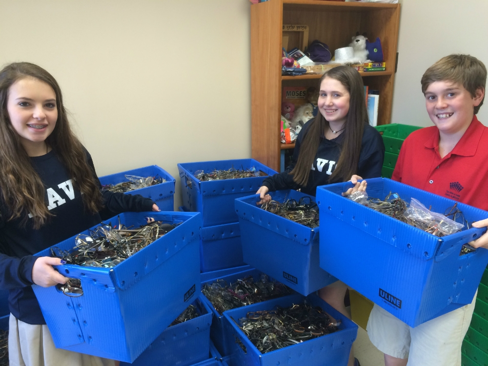 Davis academy 8th graders prepare for the volunteering day, holding a fraction of the 9000 pairs of glasses in my office.