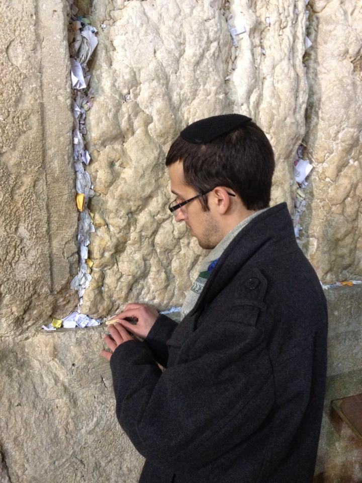 Josh inserts the prayers into a crevice in the Wall.