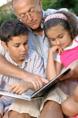 Grandfather reading to children.