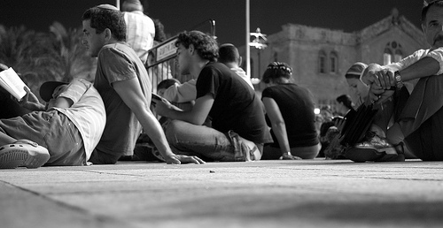 Tisha B'av service, with people sitting on tthe ground.