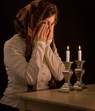 Jewish woman lighting sabbath candles