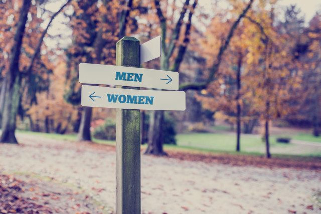 Signpost in a park or forested area with arrows pointing two opposite directions towards Men and Women.