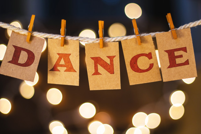 The word DANCE printed on clothespin clipped cards in front of defocused glowing lights.