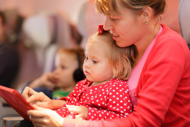 mother and little daughter looking at touch pad in plane, family travel