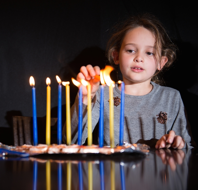 girl lights chanukiah menorah chanukah
