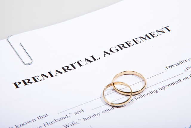 Prenuptial Agreement form and two gold wedding rings