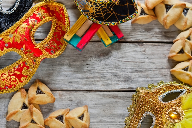 Hamantaschen cookies or Haman's ears, noisemaker and carnival masks for Purim celebration (jewish holiday). Copy space background.