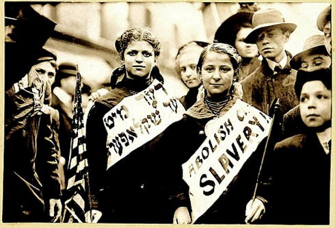 """ABOLISH CH[ILD] SLAVERY!!"" in English and Yiddish (""(ני)דער מיט (קינד)ער שקלאפער(ײ)"", ""Nider mit Kinder Schklawerii"") , probably taken during May 1, 1909 labor parade in New York City. George Grantham Bain Collection (Library of Congress)."