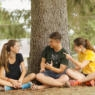 Counselors and camper talking under a tree