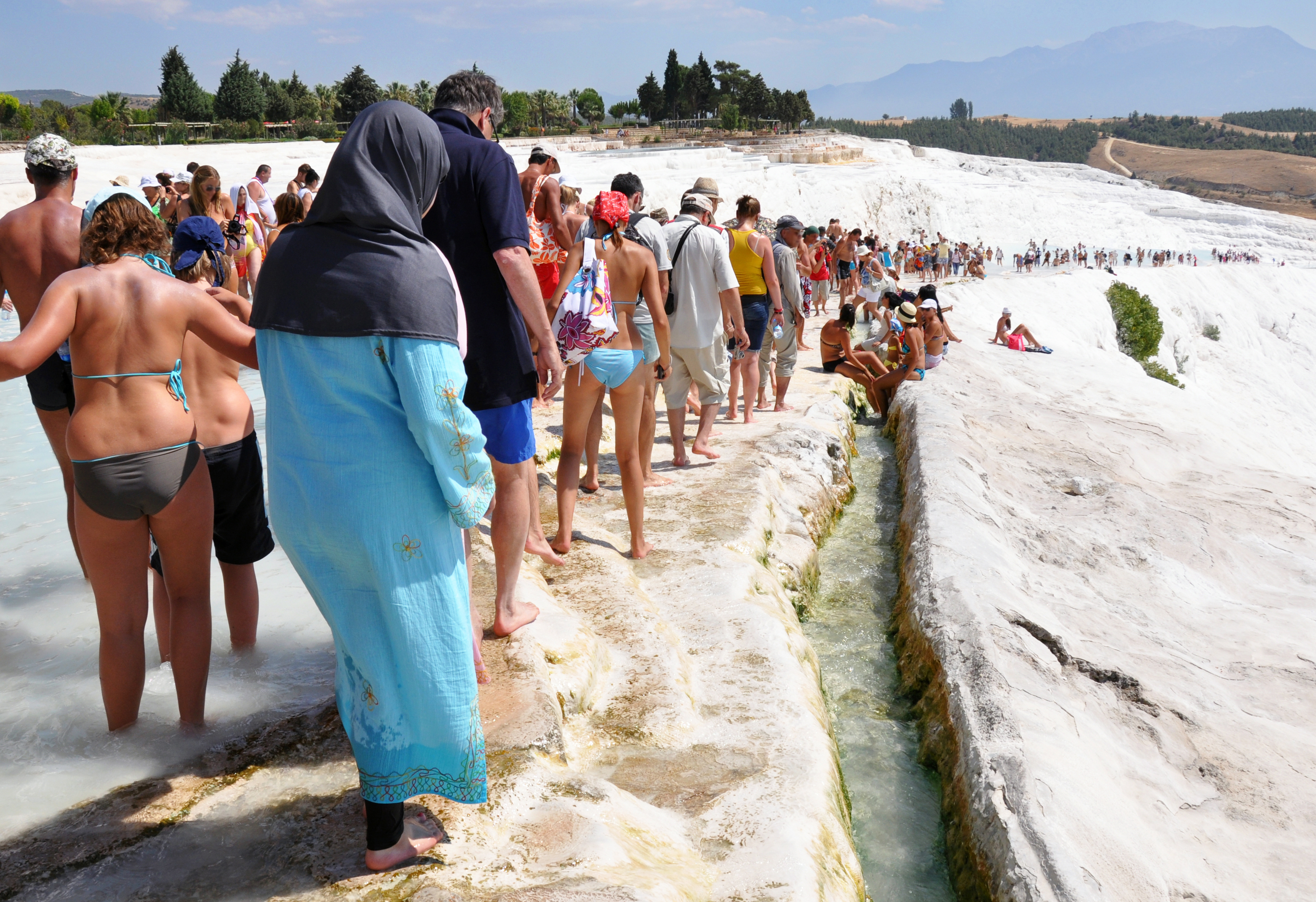 Pamukkale, Turkey - July 20, 2011: Tourists on the travertines