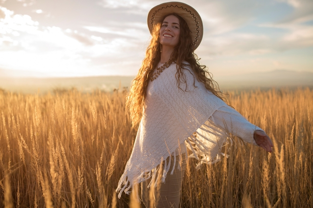 Young, beautiful woman with a straw hat and a white poncho smiling and enjoying the sun in the middle of the grass field