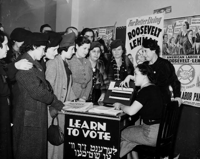 Women surrounded by posters in English and Yiddish supporting Franklin D. Roosevelt, Herbert H. Lehman, and the American Labor Party teach other women how to vote, 1936. (Wikimedia Commons)