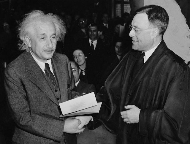 Albert Einstein accepting a U.S. citizenship certificate from Judge Phillip Forman in 1940. (Wikimedia Commons)
