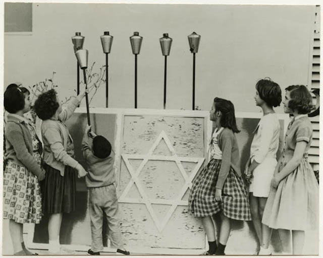 Children lighting a giant Hanukkah menorah at an American Jewish community center, circa 1950. (Courtesy of the American Jewish Historical Society)