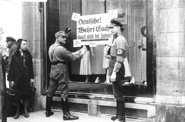 Nazis affix a sign to Jewish store urging shoppers not to patronize it, 1933. (German Federal Archives/Wikimedia Commons)