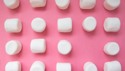 white marshmallows on a pink background.