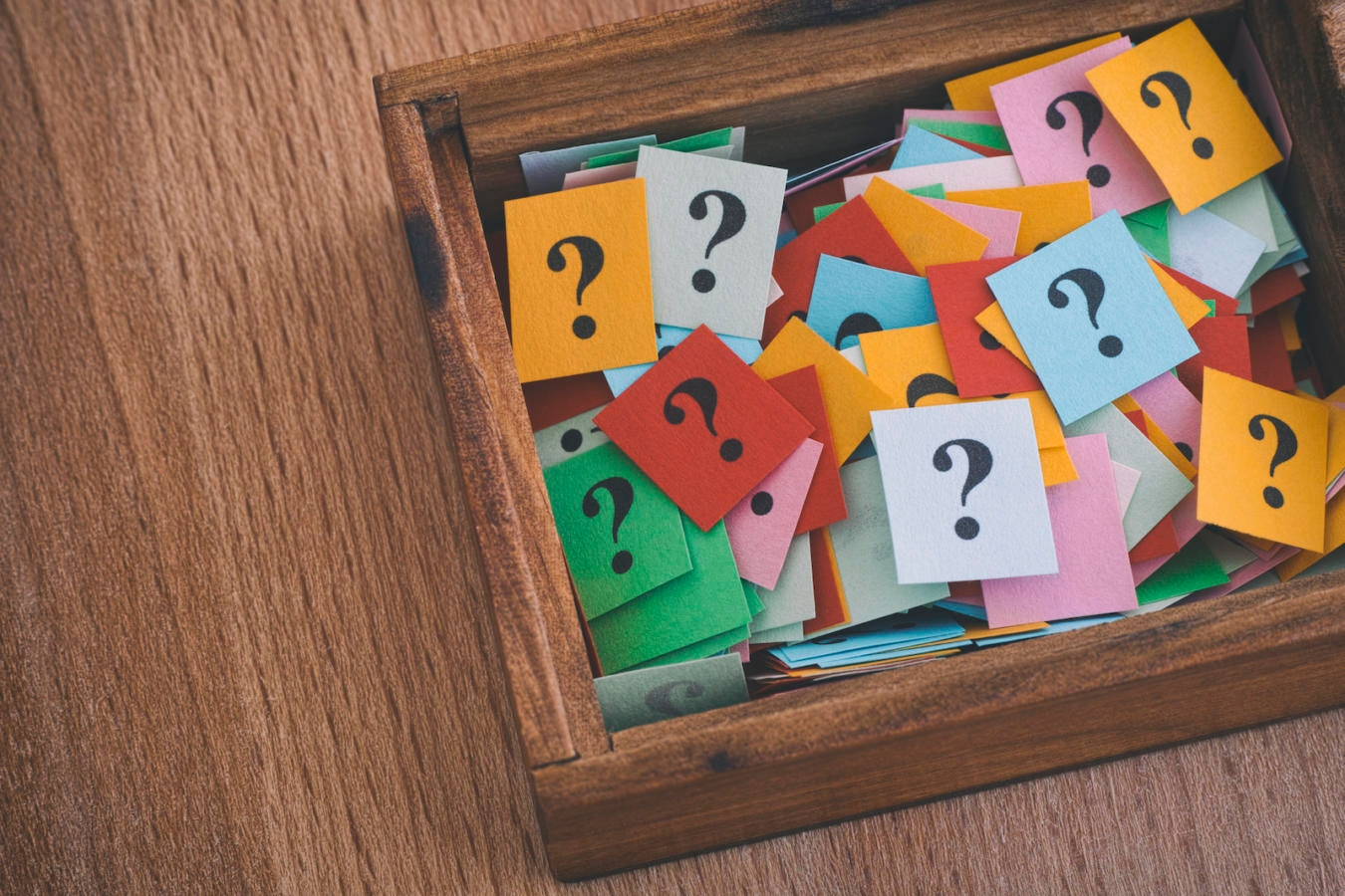 Question marks in a wooden box