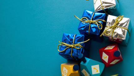 Colorful dreidels with presents on blue background.