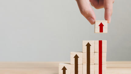 Hand arranging wood block stacking as step stair with arrow up. Ladder career path concept for business growth success process
