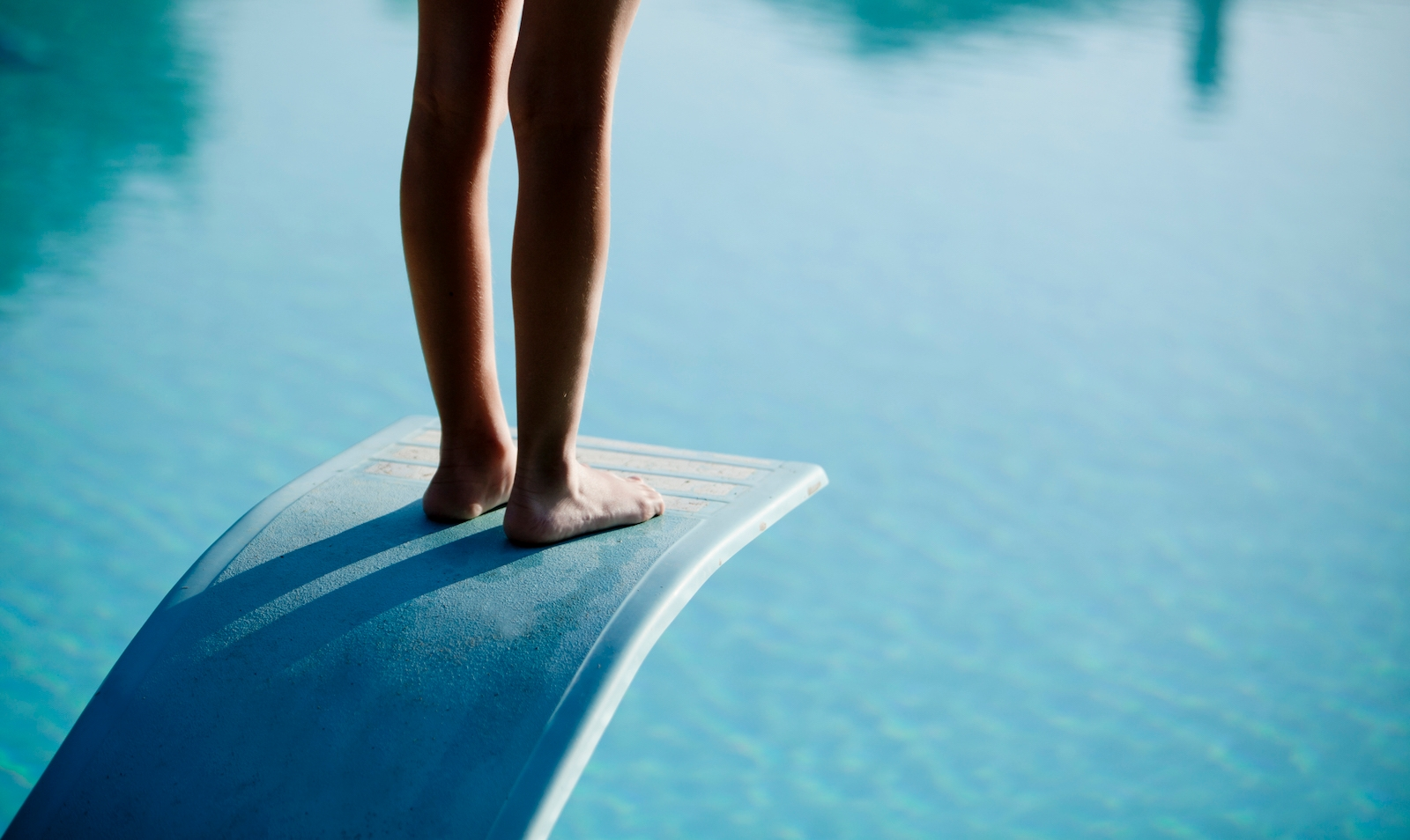 Shot of bare legs on diving board above blue water
