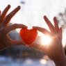 Woman hands holding red heart at sunset