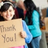 Adorable little girl holds thank you sign during food drive