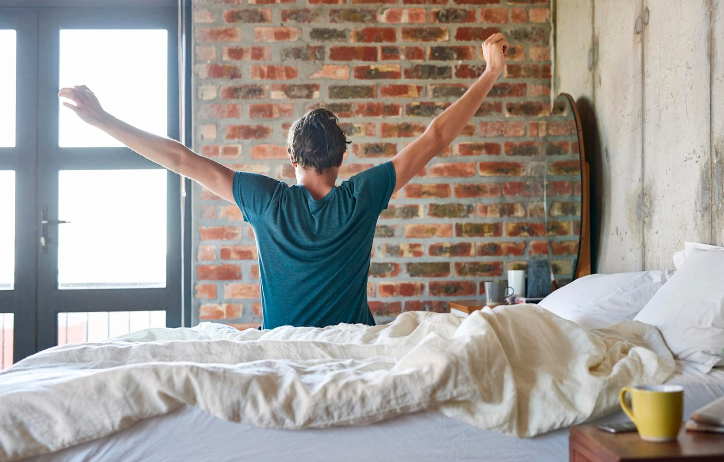 Rear view of young man stretching hands in bed