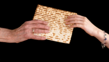 Handing a matzo from an old hand to a young hand.