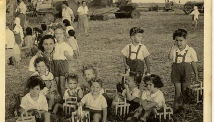 B&w photo of children in a field with flowers in their hair.