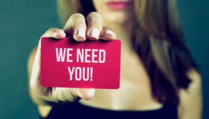 Young woman holding we need you card