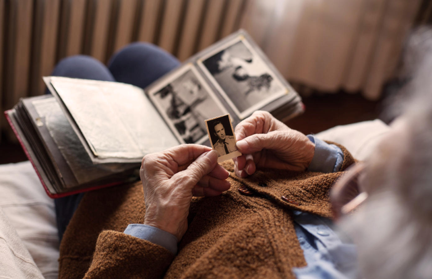 Senior adult woman looking at an old photo of her husband.