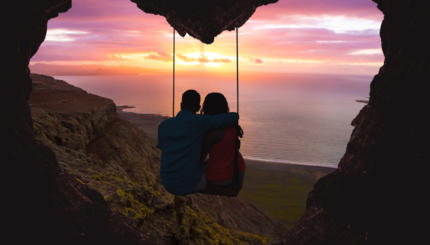 Couple on swing contemplating the sunset over the sea in a romantic view with heart shape.