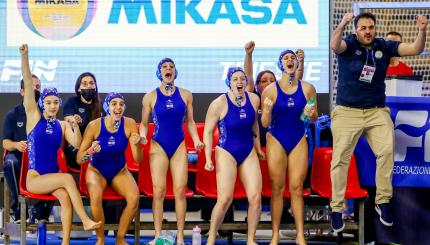 A team of women in blue bathing suits, screaming in excitement.