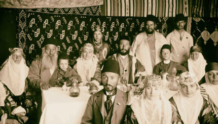 Sepia photograph of Bukharan Jews in a sukkah in traditional dress.
