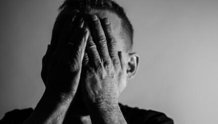 Black and white photo of a person clasping hands over their face.